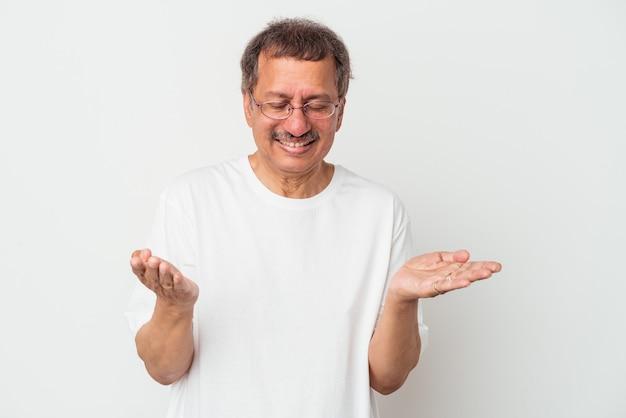 Homme indien d'âge moyen isolé sur fond blanc tenant quelque chose avec des paumes, offrant à la caméra.