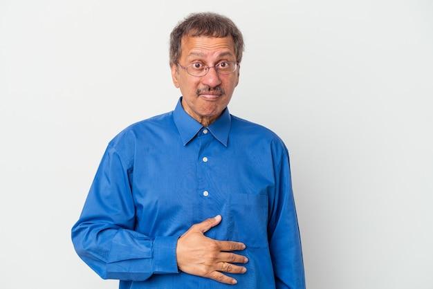 Un homme indien d'âge moyen isolé sur fond blanc touche le ventre, sourit doucement, mange et satisfait le concept.