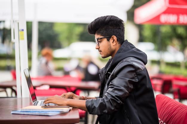 Homme indien à l'aide d'un ordinateur portable tout en buvant une tasse de café dans un café de rue en plein air