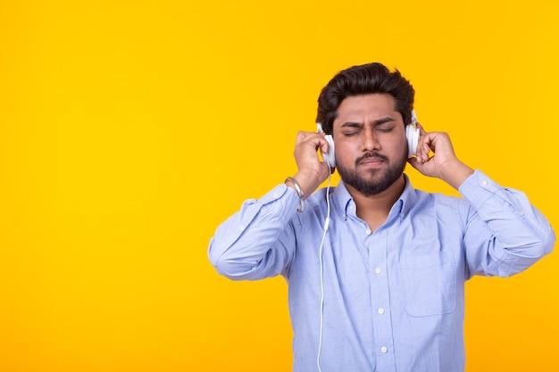 L'homme indien aime la musique dans ses écouteurs sur mur jaune