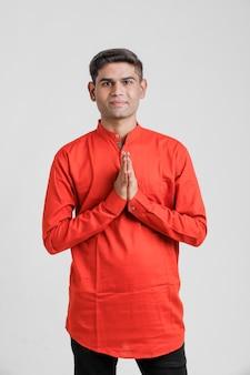 Homme indien / asiatique en chemise rouge et montrant un geste de bienvenue, isolé sur blanc