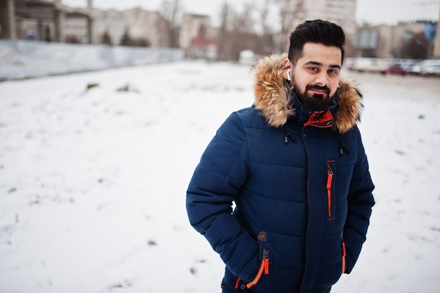 Homme indien barbe porter une veste en froide journée d'hiver. écouteurs mobiles dans les oreilles.