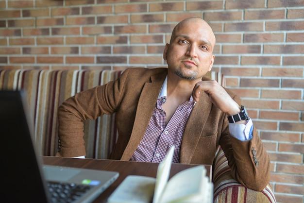 Homme indien confiant, assis au café avec ordinateur portable et ordinateur portable avec regardant sérieusement à la caméra