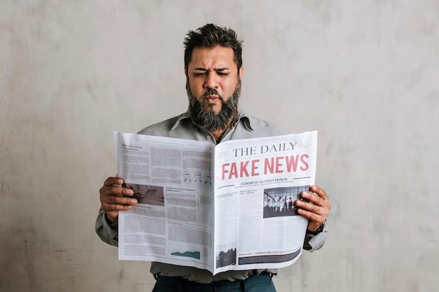 Homme indien confus lisant le journal