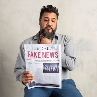 Homme indien douteux lisant le journal avec de fausses nouvelles