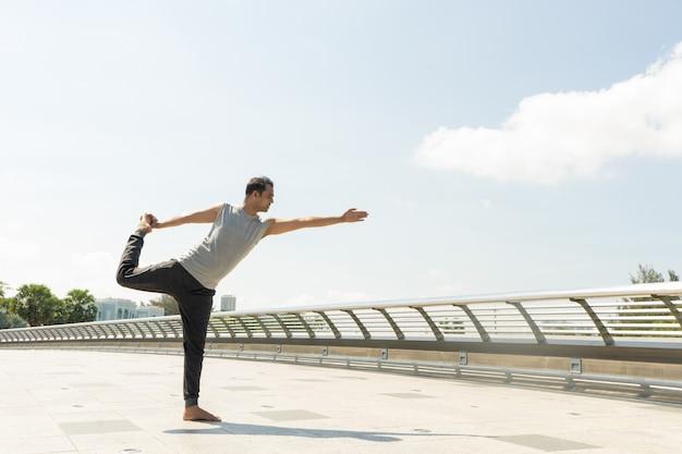 Homme indien faisant seigneur de la danse pose à l'extérieur sur le pont par une journée ensoleillée. concept d'yoga de la ville.