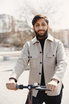 Homme indien monté sur un scooter électrique.