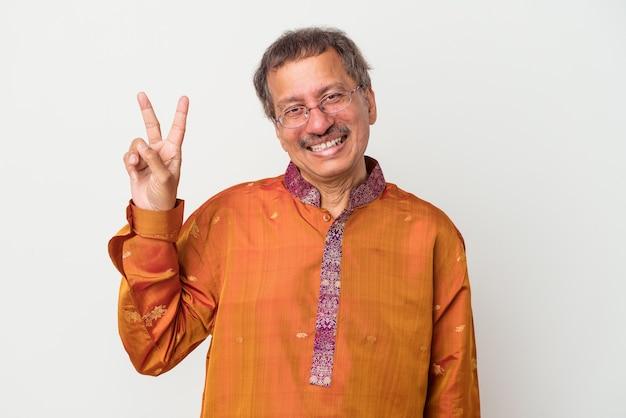 Homme indien senior portant un costume indien isolé sur fond blanc joyeux et insouciant montrant un symbole de paix avec les doigts.