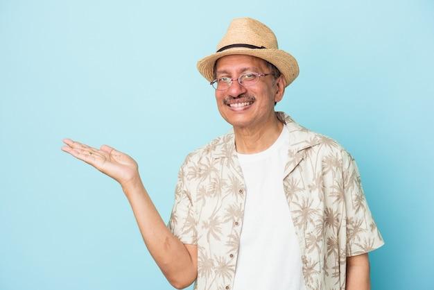 Homme indien senior portant des vêtements d'été isolé sur fond bleu