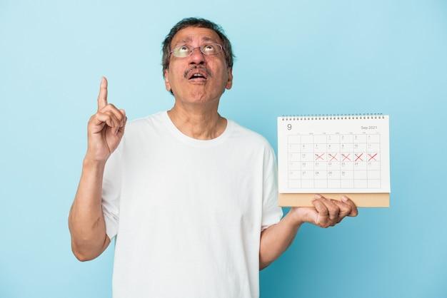 Homme indien senior tenant un calendrier isolé sur fond bleu pointant vers le haut avec la bouche ouverte.