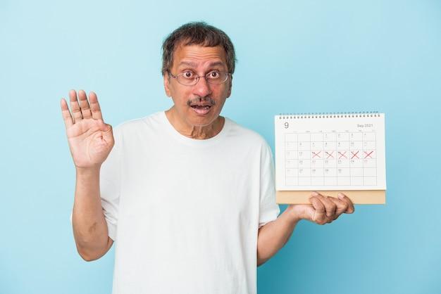 Homme indien senior tenant un calendrier isolé sur fond bleu surpris et choqué.