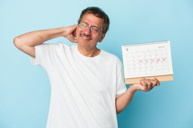 Homme indien senior tenant un calendrier isolé sur fond bleu touchant l'arrière de la tête, pensant et faisant un choix.