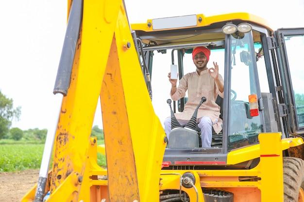 Homme indien travaillant avec des machines de terrassement lourdes et montrant l'écran du smartphone.