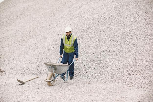 Homme indien travaillant. mâle dans un gilet jaune. homme avec brouette.