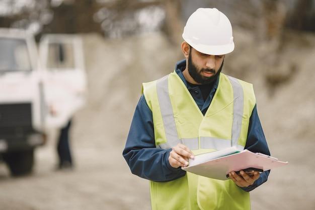 Homme indien travaillant. mâle dans un gilet jaune. homme avec dossier.