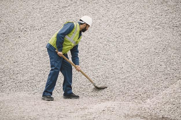 Homme indien travaillant. mâle dans un gilet jaune. homme avec une pelle /