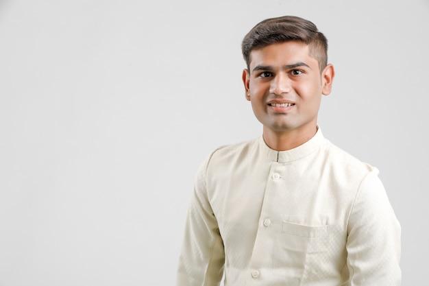 Homme indien en vêtements ethniques et debout sur blanc
