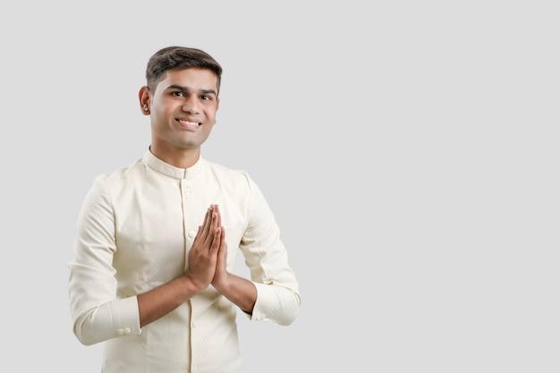 Homme indien en vêtements ethniques et montrant un geste de bienvenue isolé sur blanc