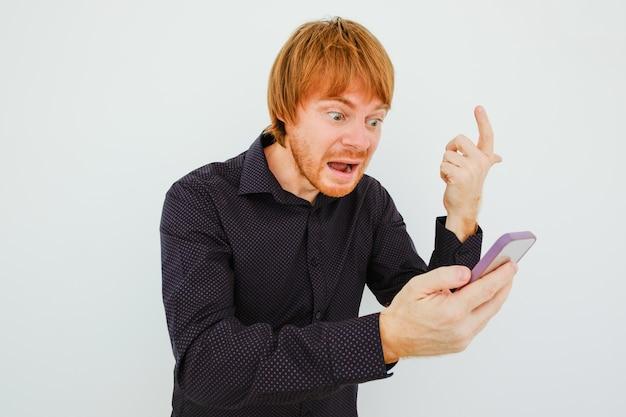 Homme indigné aux cheveux roux avec téléphone intelligent