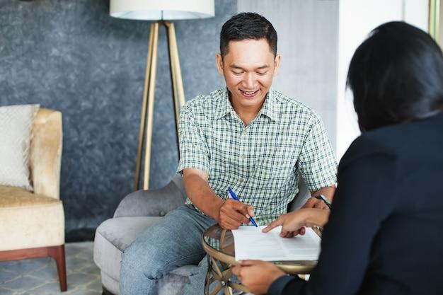 Homme indonésien signant un contrat lors d'une réunion