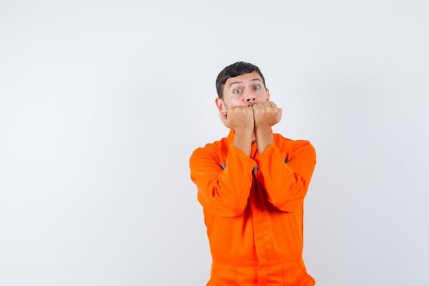 Homme industriel mordant les poings émotionnellement en uniforme et à la peur. vue de face.