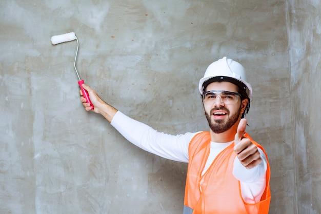 Homme ingénieur en casque blanc et lunettes de protection peignant le mur avec un rouleau de finition et montrant le pouce vers le haut.
