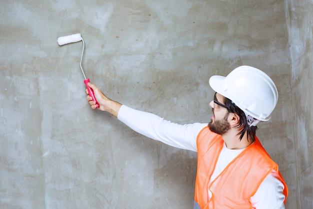 Homme ingénieur en casque blanc et lunettes de protection peignant le mur avec un rouleau de garniture blanc.