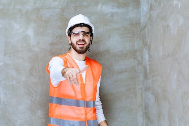 Homme ingénieur en casque blanc et lunettes de protection pointant sur son collègue ou sur quelque chose de côté.