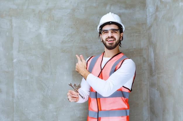 Homme ingénieur en casque blanc et lunettes de protection tenant des clés métalliques et montrant quelqu'un derrière.