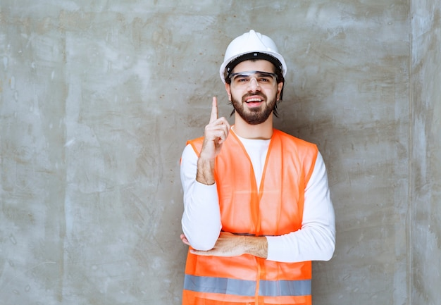 Homme ingénieur en casque blanc et lunettes de protection tenant une hache en bois.