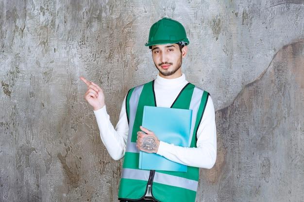 Homme ingénieur en uniforme jaune et casque tenant un dossier bleu et pointant vers la gauche.