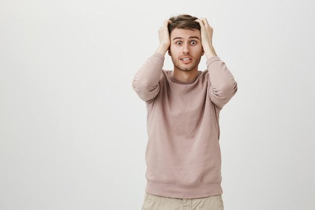 Homme inquiet alarmé jetant les cheveux et serrant les dents dans la panique