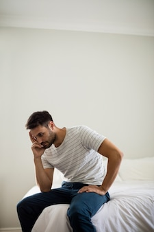Homme inquiet assis dans la chambre à la maison