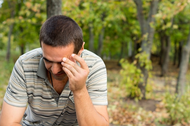 Homme inquiet assis seul à l'extérieur avec sa main sur son front