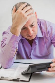 Homme inquiet calculant l'impôt sur fond blanc