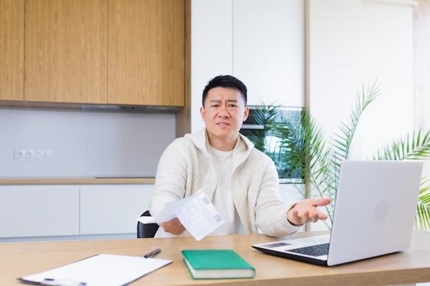 Homme inquiet et stressé calculant les dépenses fiscales des factures et comptant les finances de la maison