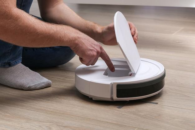 Un homme insère un filtre et un récipient pour collecter la poussière et les débris dans un aspirateur robot.