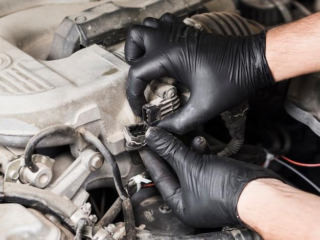 Homme inspectant le câblage du moteur