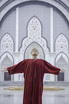 Homme inspiré en rouge regardant vers le ciel avec les bras tendus sur les côtés