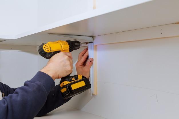 Homme installant des étagères en bois sur des supports muraux installant une étagère