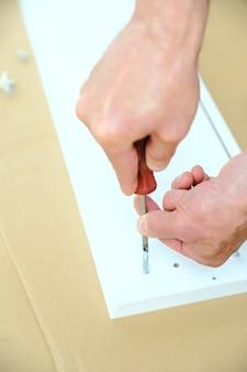 Un homme installe des boulons de connecteur commun dans le panneau de meuble.