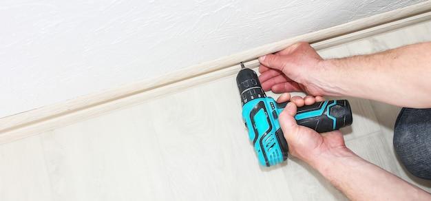 L'homme installe la plinthe avec une perceuse. la réparation fonctionne à l'intérieur. rénovation dans l'appartement.