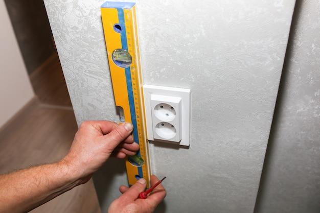 L'homme installe la prise. niveau à bulle dans les mains. travaux de réparation d'entretien d'électricité dans l'appartement. restauration à l'intérieur.