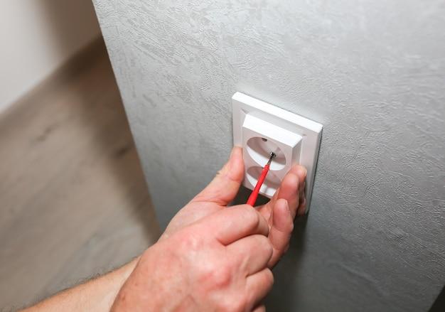 L'homme installe la prise. travaux de réparation d'entretien d'électricité dans l'appartement. restauration à l'intérieur.