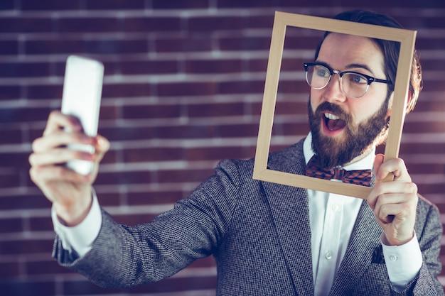 Homme intelligent prenant selfie tout en maintenant le cadre
