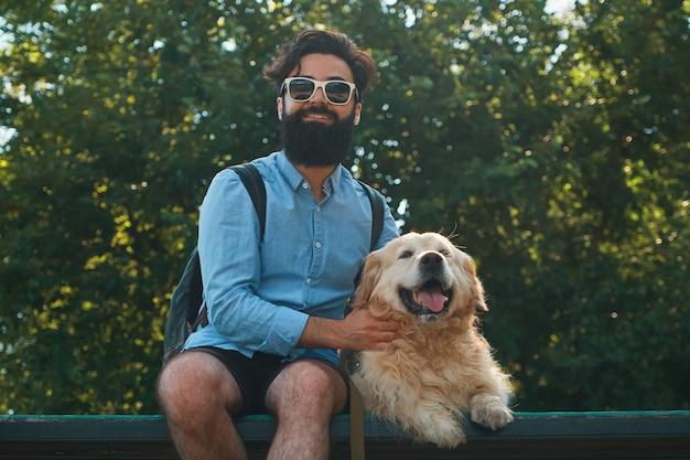 Homme intéressant assis avec son chien sur la chaise dans le parc