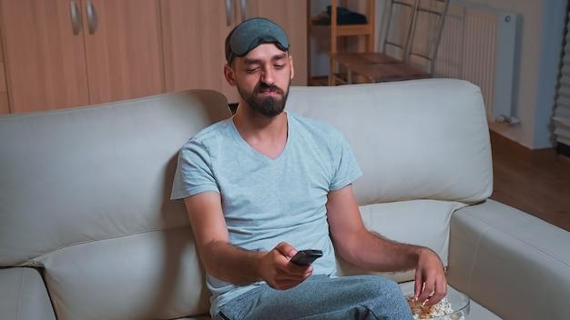 Homme intéressé avec barbe se relaxant devant la télévision tout en regardant un film de divertissement
