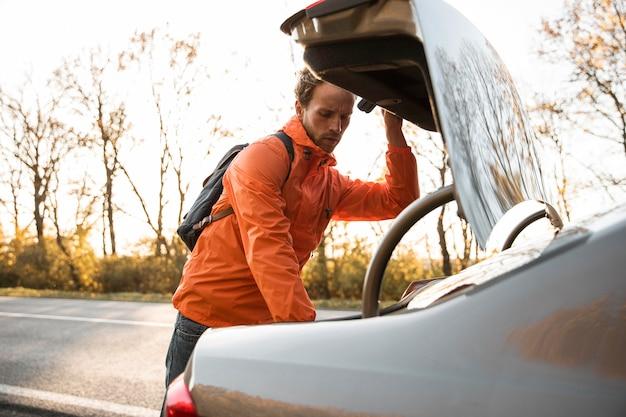 L'homme à l'intérieur du coffre de la voiture lors d'un voyage sur la route