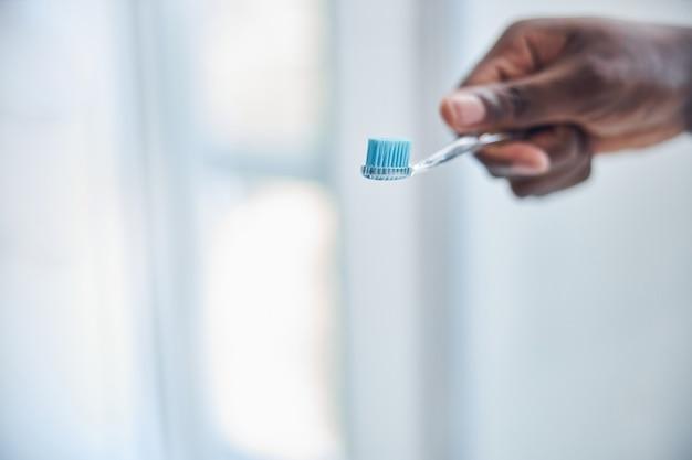 Un homme international aimable étant à la maison et passant sa matinée dans la salle de bain tout en prenant soin de ses dents