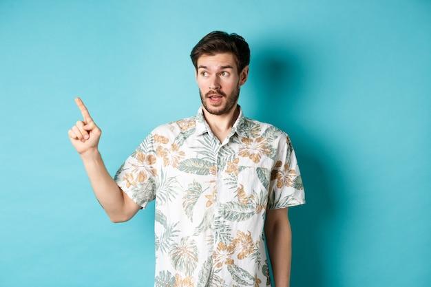 Homme intrigué en chemise hawaïenne, regardant et pointant vers la gauche quelque chose d'intéressant, fond bleu. concept de tourisme et de vacances.